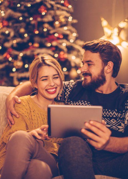 Couple sur canapé - Tablette connectée - Noël
